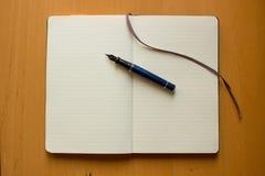Pluma en el cuaderno Imagen de archivo