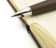 Pluma en el cuaderno Fotografía de archivo libre de regalías