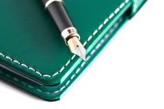 Pluma en el cuaderno Imágenes de archivo libres de regalías