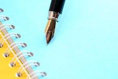 Pluma en el cuaderno Imagen de archivo libre de regalías