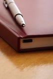 Pluma en el cuaderno fotos de archivo