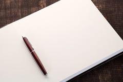 Pluma en el cuaderno abierto Imagen de archivo libre de regalías