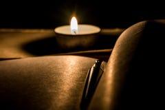 Pluma en el cuaderno al lado de la vela