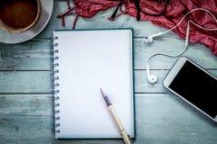 Pluma en el cuaderno, el teléfono móvil, el auricular y el café Imagen de archivo