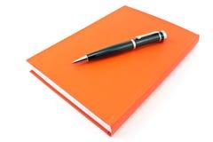 Pluma en el cuaderno rojo Fotos de archivo libres de regalías