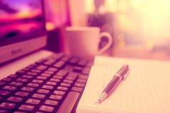Pluma en el cuaderno y el ordenador Foto de archivo