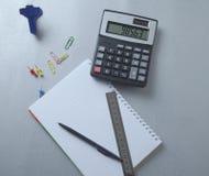 Pluma en el cuaderno y la calculadora imagen de archivo