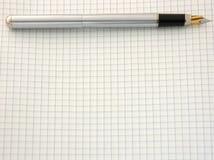 Pluma en el papel ajustado en blanco Fotos de archivo libres de regalías