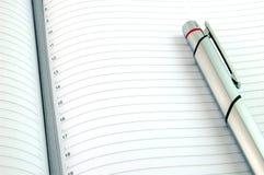 Pluma en el papel alineado en blanco Imagen de archivo
