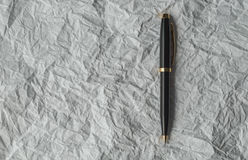 Pluma en el papel arrugado Foto de archivo libre de regalías