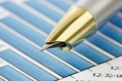 Pluma en gráficos financieros Imágenes de archivo libres de regalías