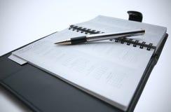 Pluma en planificador del día laboral Imagen de archivo