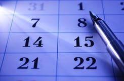 Pluma en un calendario Foto de archivo libre de regalías