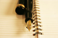 Pluma en un cuaderno Fotos de archivo libres de regalías