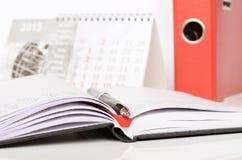 Pluma en un cuaderno abierto y un calendario Imágenes de archivo libres de regalías