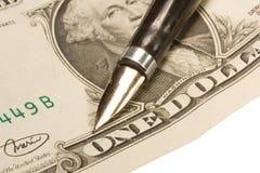 Pluma en una cuenta de dólar Foto de archivo libre de regalías