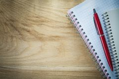 Pluma espiral del biro de los cuadernos en el tablero de madera imagenes de archivo