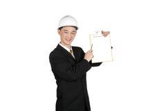 Pluma joven asiática del uso del ingeniero que señala a su tablero Imagen de archivo