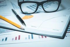 Pluma, lápiz, vidrios en el papel de carta del gráfico de negocio imagen de archivo libre de regalías