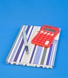 Pluma, libro y calculadora solar. Foto de archivo libre de regalías