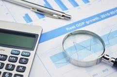 Pluma, lupa y calculadora en el gráfico financiero, cuenta Foto de archivo