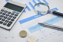 Pluma, lupa y moneda en carta y gráfico financieros Imagenes de archivo