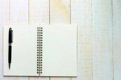 Pluma negra en el cuaderno Imágenes de archivo libres de regalías