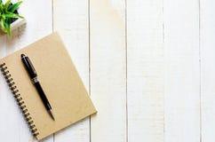 Pluma negra en el cuaderno marrón Imágenes de archivo libres de regalías