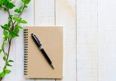 Pluma negra en lugar marrón del libro en la tabla Fotos de archivo libres de regalías