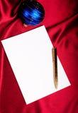 Pluma, papel y bola azul. Fotografía de archivo