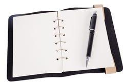 Pluma que descansa sobre un cuaderno de notas en blanco Imagenes de archivo
