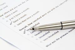 Pluma que señala en la encuesta y la forma del cuestionario Imágenes de archivo libres de regalías