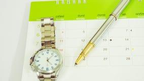 Pluma, reloj y calendario en la tabla blanca fotografía de archivo libre de regalías