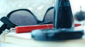 Pluma roja que pone en el cuaderno, las gafas de sol y la otra materia, borrosos Imagen de archivo libre de regalías