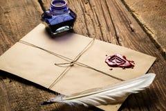 Pluma, sobre, cera de lacre y botella de tinta viejos Foto de archivo libre de regalías