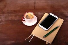 Pluma vacía del cuaderno y de bola con una taza del café, teléfono del escritorio de oficina Concepto del asunto Imagen de archivo libre de regalías