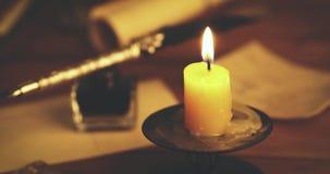 Pluma y artículos vintages retros de la pluma en la tabla en luz de una vela almacen de video