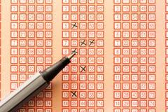 Pluma y boleto de lotería de la loteria del bingo con números cruzados Fotos de archivo libres de regalías