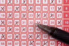 Pluma y boleto de lotería de la loteria del bingo con números cruzados Imagen de archivo libre de regalías