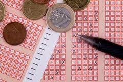 Pluma y boleto de lotería de la loteria del bingo con números cruzados, dinero euro Imagen de archivo