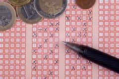 Pluma y boleto de lotería de la loteria del bingo con números cruzados, dinero euro Imagenes de archivo