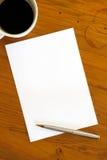 Pluma y café del papel en blanco