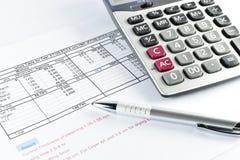 Pluma y calculadora colocadas en el documento Imagen de archivo libre de regalías