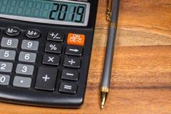 Pluma y calculadora con el número 2019 en la exhibición en la tabla de madera en la tabla de madera Fotografía de archivo libre de regalías