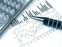 Pluma y calculadora contra el gráfico (en azul) foto de archivo