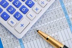Pluma y calculadora en la hoja con números Fotos de archivo