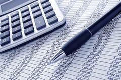 Pluma y calculadora en la hoja de balance financiera Fotografía de archivo libre de regalías
