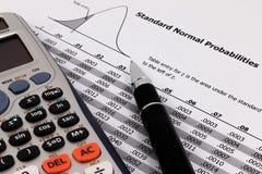 Pluma y calculadora en la tabla normal estándar de las probabilidades Fotografía de archivo libre de regalías