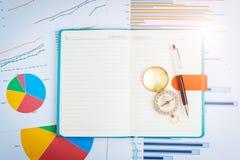 Pluma y compás en el cuaderno, gráficos, cartas, tabla del negocio E Fotos de archivo libres de regalías