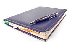 Pluma y cuaderno azul Fotografía de archivo libre de regalías